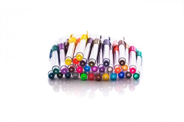 Groep kleurrijke schoolpennen die op wit voor terug naar school wordt geïsoleerd.