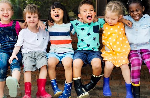 Groep kleuterschool kinderen vrienden arm rond zitten en glimlachend plezier