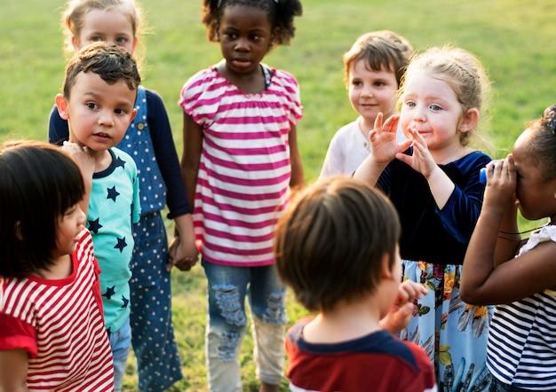 Groep kleuterschooljonge geitjesvrienden die handen houden die bij park spelen