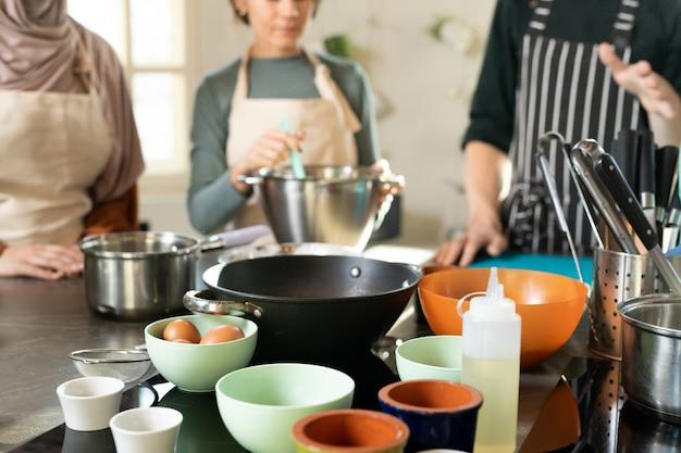 Groep kommen met ingrediënten op de keukentafel op de achtergrond van een kookcoach in een gestreept schort die leerlingen uitlegt hoe ze moeten koken