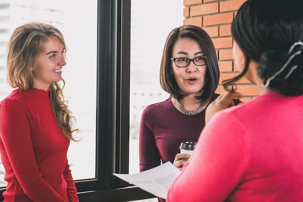 Groep krachtige diverse vrouwen in vrijetijdskleding die samen spreken