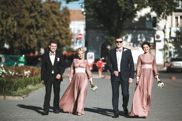 Groep lachende bruidsmeisjes en bruidsmeisjes lopen