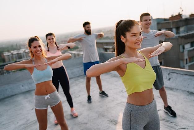 Groep lachende, fitte, gelukkige mensen die buiten krachttraining doen