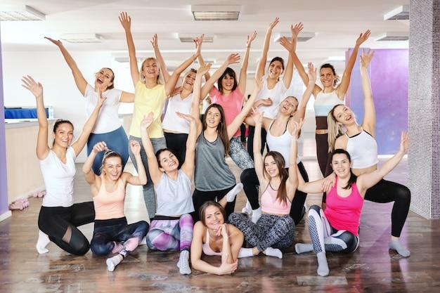 Groep lachende gezonde fit vrouwen zwaaien en poseren in de sportschool na het sporten.