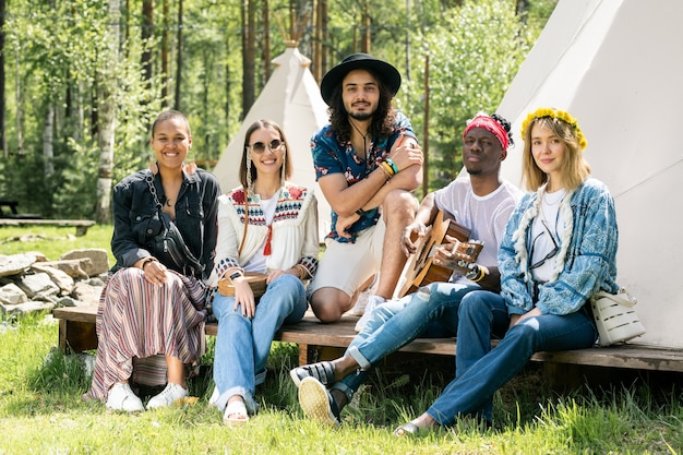 Groep lachende jonge multi-etnische vrienden zittend op de veranda van camping tent en camera kijken terwijl ze samen rusten
