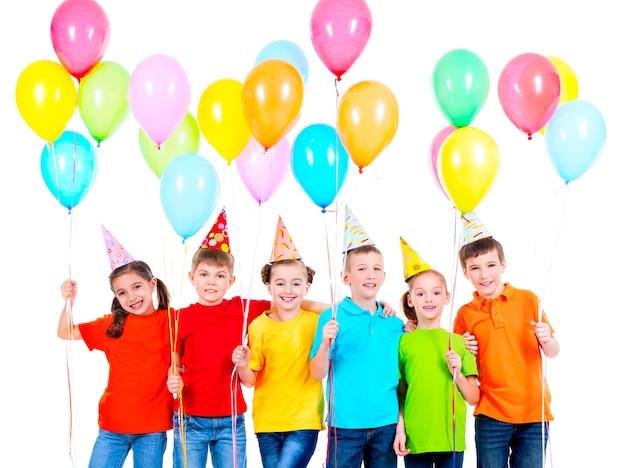 Groep lachende kinderen in gekleurde t-shirts en feestmutsen met ballonnen op een witte achtergrond