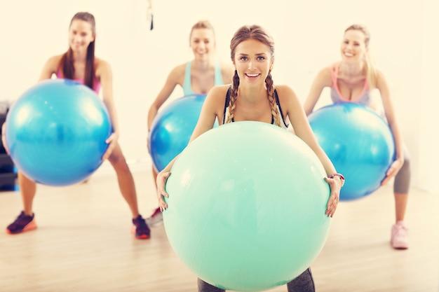 Groep lachende mensen die aerobics doen met ballen