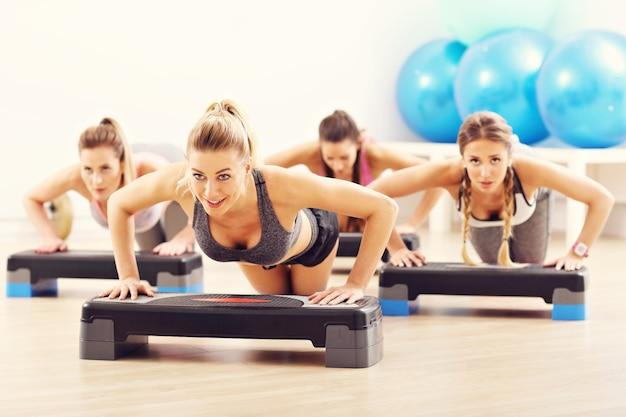 Groep lachende mensen die push-ups doen