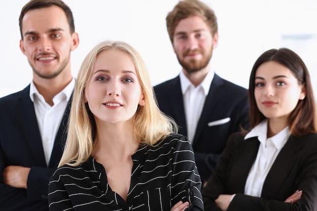 Groep lachende mensen staan op kantoor in de camera te kijken
