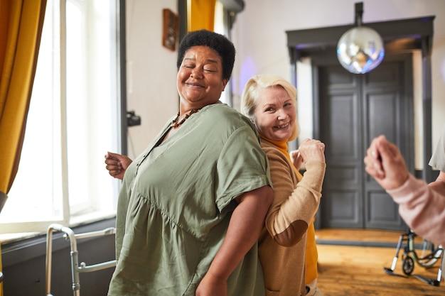 Groep lachende oudere vrouwen die dansen terwijl ze genieten van activiteiten in het bejaardentehuis, kopieer ruimte