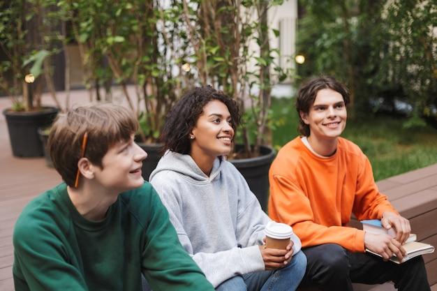 Groep lachende studenten zitten met koffie om te gaan en boeken in handen en dromerig opzij kijken terwijl ze samen studeren op de binnenplaats van de universiteit