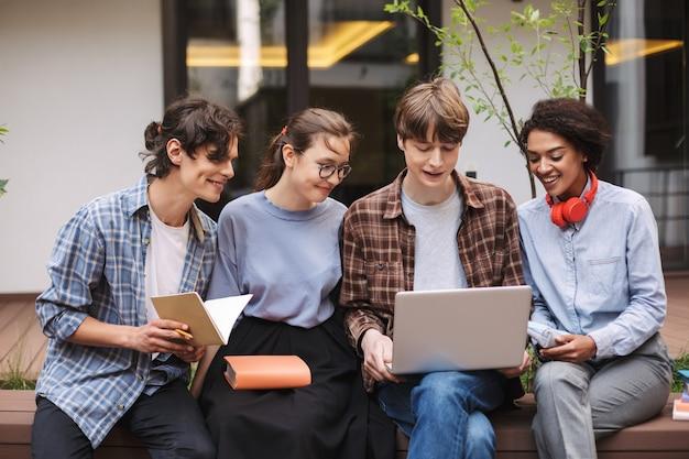 Groep lachende studenten zittend op een bankje met laptop en boeken op de binnenplaats van de universiteit