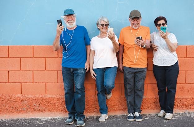 Groep lachende volwassen mensen die buiten staan met behulp van mobiele telefoon met oortelefoons. vier ouderen genieten van pensioen en plezier