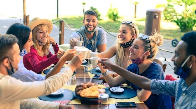 Groep lachende vrienden dragen beschermingsmasker roosteren koffie en cappuccino in café