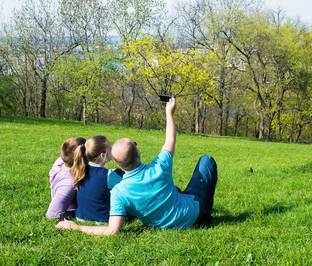 Groep lachende vrienden met smartphone zittend op het gras en selfie te nemen in het park