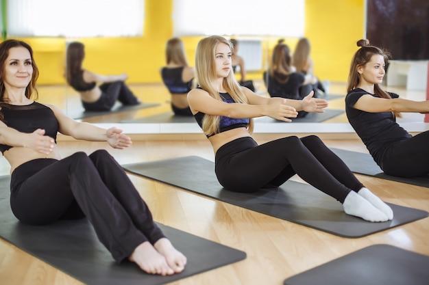 Groep lachende vrouwen oefenen op matten in de sportschool.