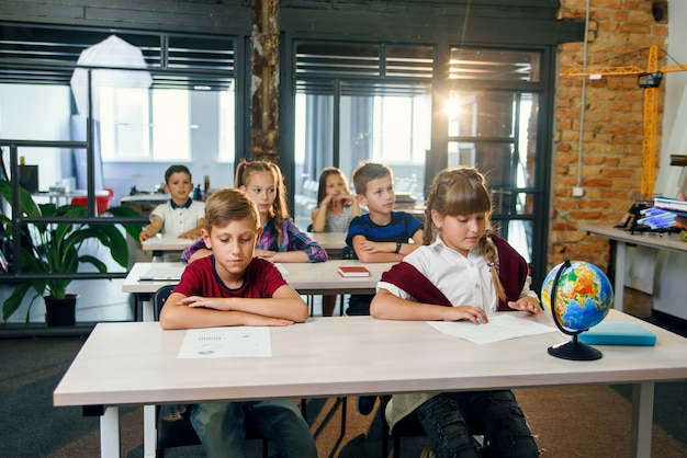 Groep leerlingen basisschool zitten aan de tafels en slagen voor examen in de klas van de moderne slimme school.