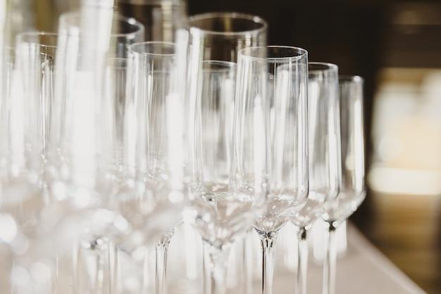 Groep lege en transparante champagneglazen in een restaurant.