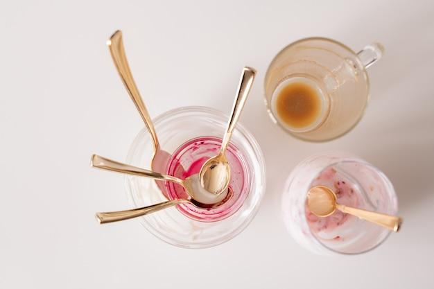 Groep lege ongewassen glazen en theelepels op keukentafel na het ontbijt bestaande uit koffie en yoghurt met zelfgemaakte jam