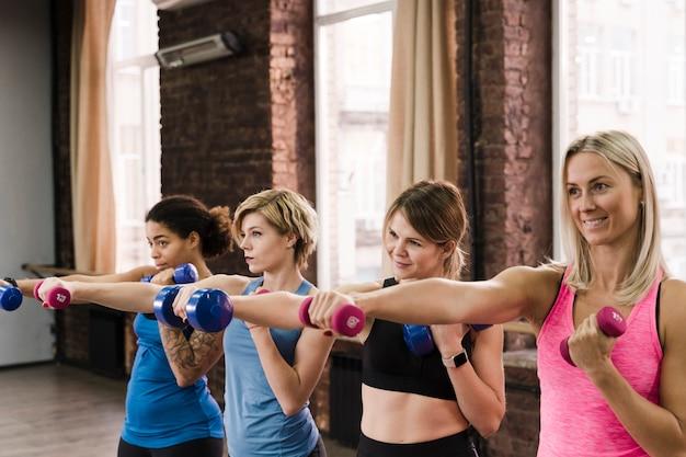 Groep leuke volwassen vrouwen die bij de gymnastiek uitwerken