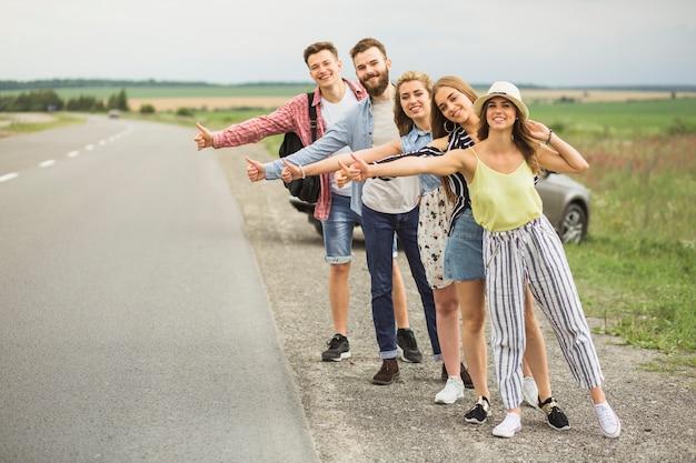 Groep lifters die op auto op plattelandsweg wachten