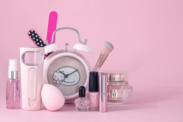 Groep make-upcosmetica met ronde klok op roze achtergrond