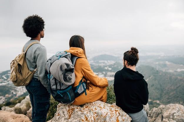 Groep mannelijke en vrouwelijke wandelaarzitting op rots die bergmening bekijken