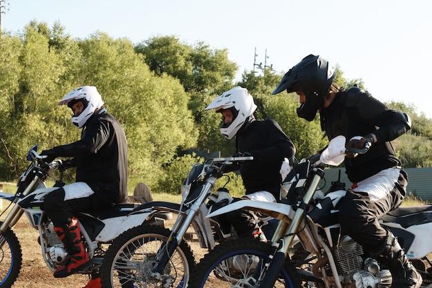 Groep mannelijke motorrijders in helmen die bij de startlijn zijn tijdens het voorbereiden van de race