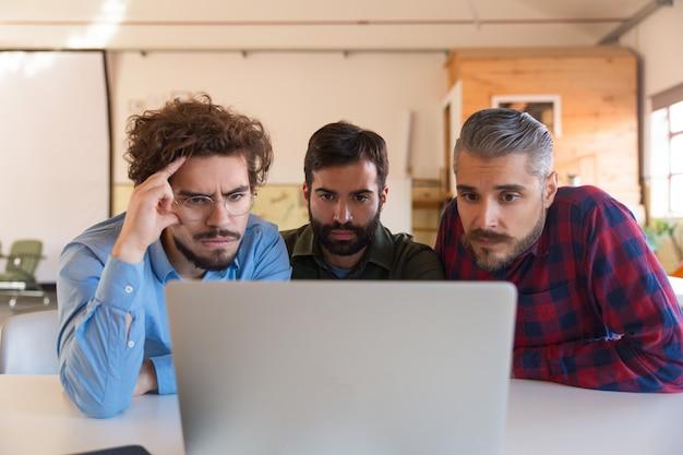 Groep mannelijke ondernemers in casual staren naar laptop monitor