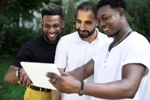 Groep mannelijke vrienden die een apparaat bekijken