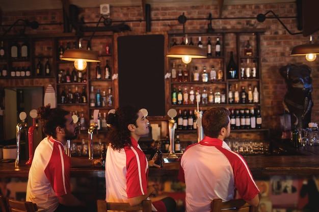 Groep mannelijke vrienden kijken naar voetbalwedstrijd