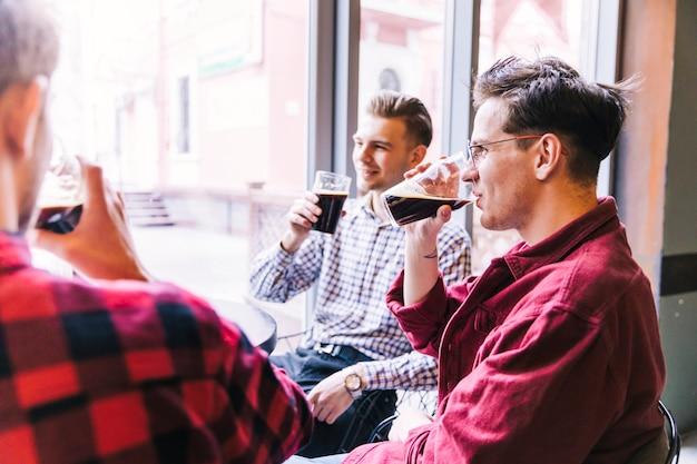 Groep mannen die het bier in de bar drinken