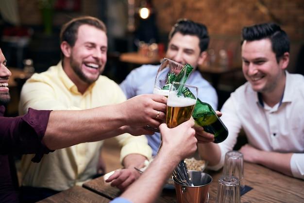 Groep mannen die juichen aan de bar