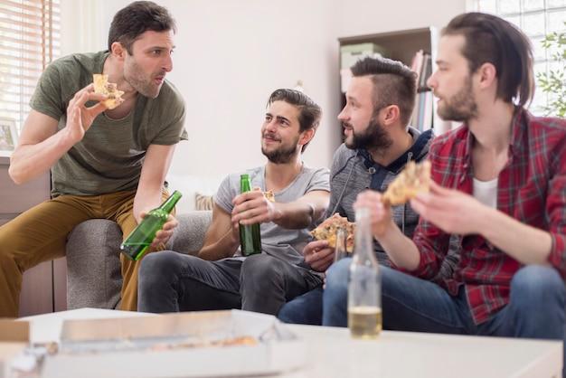 Groep mannen die pizza eten en een biertje drinken
