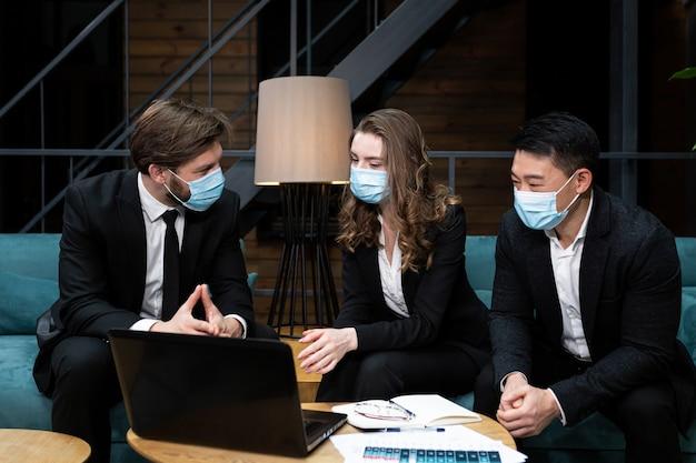 Groep mannen en vrouwen houden zakelijke bijeenkomst in de buurt van laptop met beschermende medische maskers op gezicht in conferentieruimte