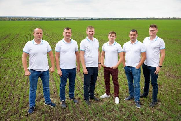Groep mannen poseren in een veld met gewassen
