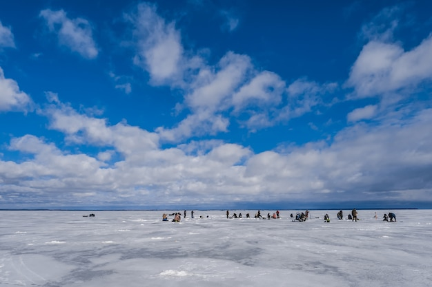 Groep mannen vissers die in de winter op het ijs van de rivier vissen