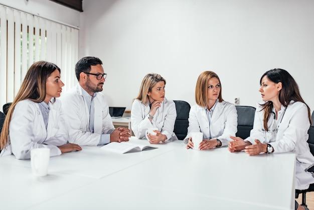 Groep medisch personeel dat in een vergadering spreekt.