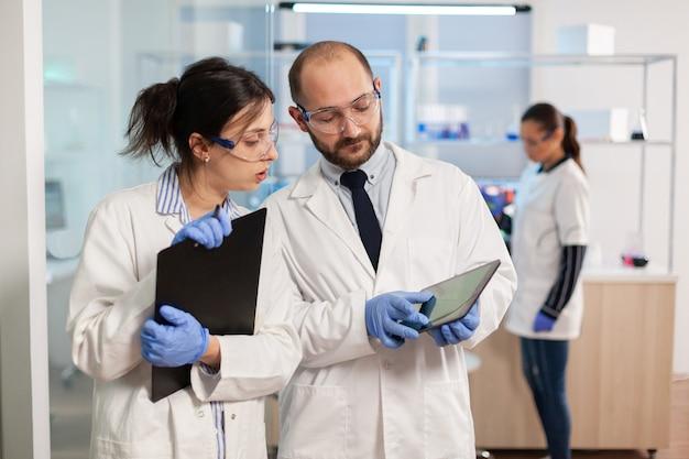 Groep medische onderzoekers die discussiëren over de ontwikkeling van vaccins, in een uitgerust laboratorium staan, wijzend op een tablet en aantekeningen maken
