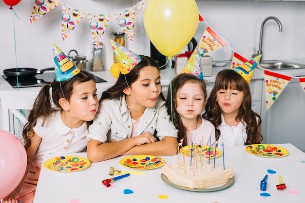 Groep meisjes die kaarsen op verjaardagscake blazen