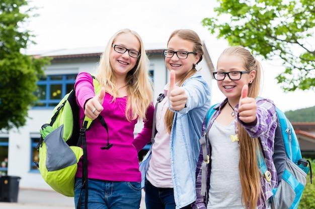 Groep meisjes die zich voor school bevinden