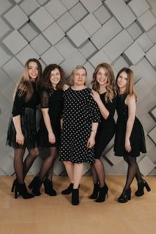 Groep meisjes in zwarte jurken op grijze geweven muur