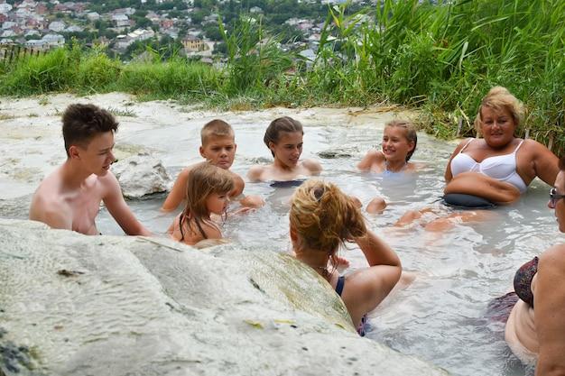 Groep mensen baadt in hete minerale bronnen. zwembad met thermisch nuttig water.