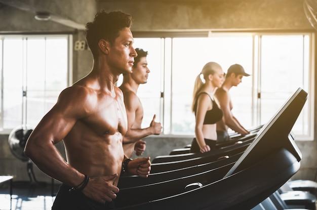 Groep mensen bij de gymnastiek die op de machine van de tredmolentrainer uitoefent. jonge fitness mannen en vrouwen die cardiotrainingprogramma voor beginner doen.