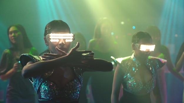 Groep mensen dansen in disco nachtclub op het ritme van muziek van dj op het podium