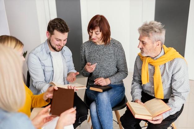 Groep mensen die boeken lezen tijdens therapiesessie