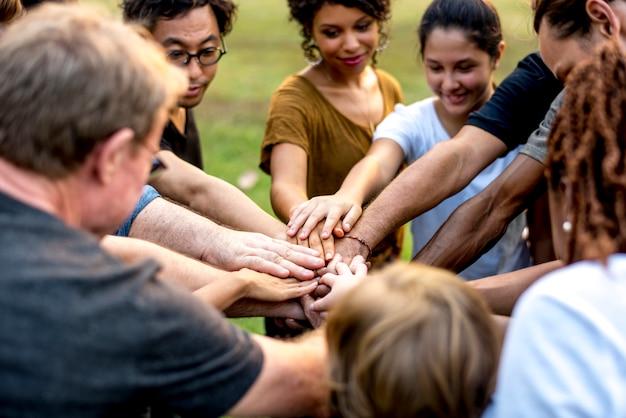 Groep mensen die hand houden samen te stellen