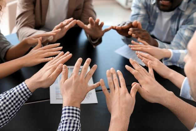 Groep mensen die handen binnenshuis samenstellen. eenheid concept