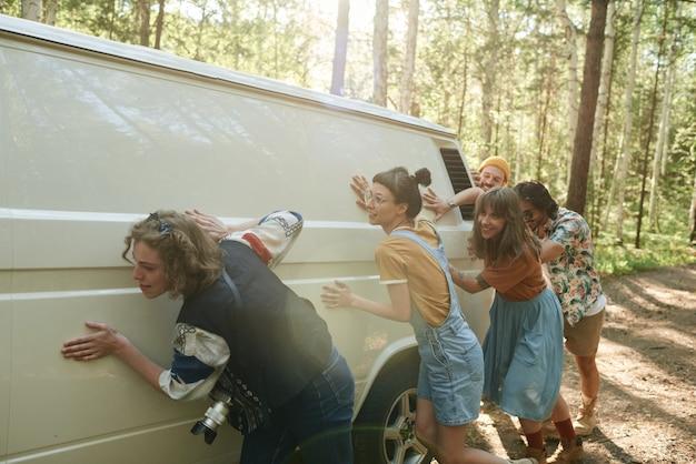 Groep mensen die het busje samen duwen tijdens een reis door de natuur