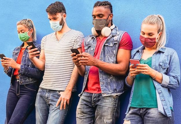 Groep mensen die hun smartphones gebruiken in covid 19 keer beschermd met gezichtsmasker - vrienden die online nieuws controleren terwijl ze bij de muur staan en mobiele telefoons vasthouden